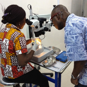 Two people are leaning over a small table with medical tools on it. The one on the left is looking through a microscope practising something on a plastic face mould, while the other is observing her.