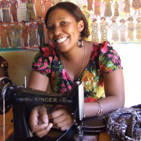 A picture of a woman at a table with a sewing machine on it. She is looking at the camera and smiling.