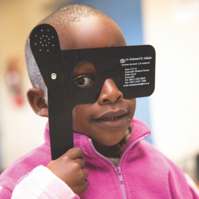 A close up of a young girl in a pink jumper, holding up a black glasses occluder to cover one of her eyes.