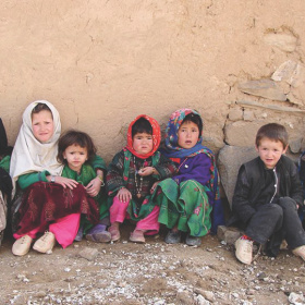 A picture of five young children sat against a crumbling wall with rubble on the ground in front of them.