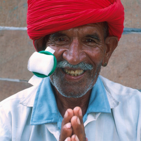 A close up picture of an older man with a eye patch stuck to his face, which has been removed to show his eye. He is smiling and holding his hand together in front of him.