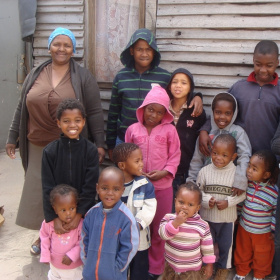 A group of children of varying ages are standing together in front of a wooden wall, with a woman next to them, who is smiling.