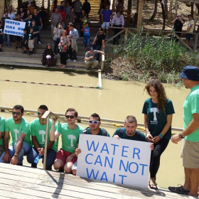 A group of young adults are kneeling in front of a murky looking river wearing matching t-shirts. Two of them are holding a sign saying 'Water cannot wait'. In the background, on the other side of the river are more people watching, one of them holding a