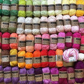 A close up of multicoloured balls of yarn arranged on a table.