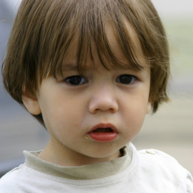 A close up picture of a young boy with long hair and big eyes, looking sad.