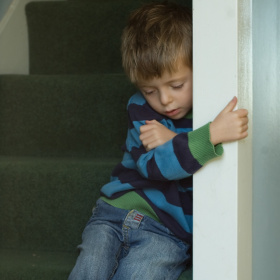 A picture of a young boy sat on a flight of stairs, holding onto the wall next to him tightly and looking sad.