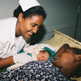 A nurse is smiling and leaning over a woman and her new born baby.