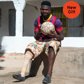 A young man is sat on a slab of concrete holding a football in his hands. He is wearing shorts and one of his legs is prosthetic.