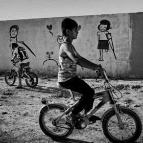 A black and white picture of a young boy on a bike, behind him is a wall with cartoon drawings of people who are missing limbs and using crutches.