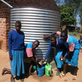 Four teenagers are standing in front of a large silver water tank, three of them are bent down filling up watering cans with water.