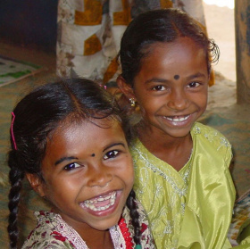 A picture of two young Indian girls looking into the camera and smiling widely.