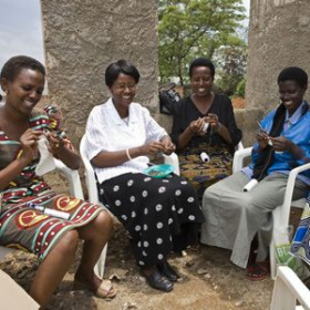 Four women are sat in a semi circle knitting outdoors, they are all smiling and look very happy.
