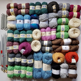 A picture of lots of different coloured balls of yarn laid out on a white background. To the left are several pairs of crochet hooks and knitting needles.