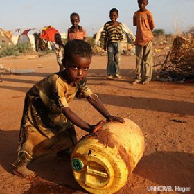 A picture of a young child in tattered clothes rolling a big plastic jug and looking at the camera. In the background there are three other children looking on and behind them what looks like a refugee camp.