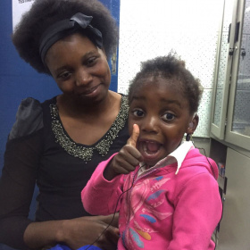 A mother is holding her young daughter who has hearing aids in her ears and is giving a big, excited thumbs up.