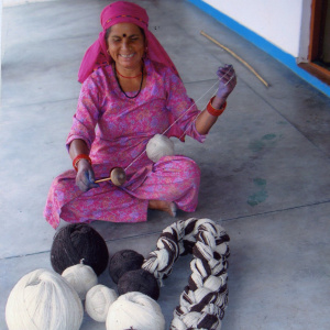A woman is sat crosslegged on the floor, with several large balls of yarn in front of her. She has one ball of white yarn in her lap and is threading it through a small wooden object in her hand.