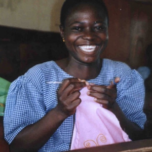 A picture of a young woman holding a pink cloth in her hands and a needle. She is smiling and looks very happy.