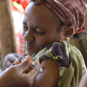 A close up picture of a woman receiving an injection in her arm and squeezing her eyes tight shut in pain.