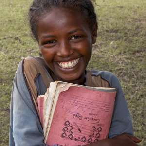A close up shot of a young girl holding some notebooks to her chest, with a big smile on her face.
