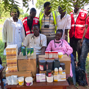 Five people wearing medical clothes are standing in a row, with two people wearing stethoscopes around their necks sat on chairs in front of them. In front of the whole group is a table piled high with boxes ad tubs of medicines.