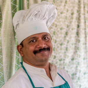 A headshot of a man with a moustache wearing a chef's hat. He is smiling and looks very happy.