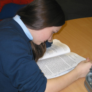 A picture of a teenage girl sat at a table bent over a book.