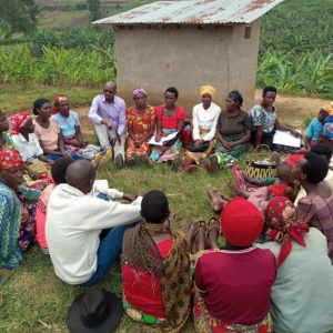 A picture of a group of people sat in a circle, engaged in discussion. Crops are visible behind them in the background.