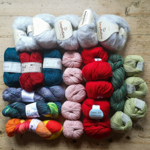 A picture of lots of balls and hanks of yarn laid out on a table.