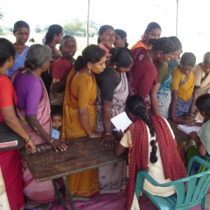 A queue of women of all ages standing in front of a table where there are two people filling out forms.