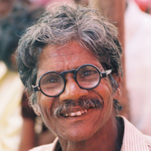 A headshot of an elderly man with greying hair and a moustache, wearing black-rimmed glasses and smiling.