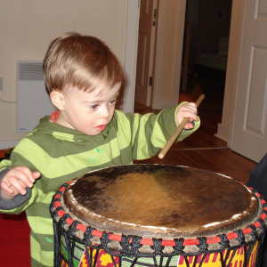 A young child is holding a drumstick and using it to bang a large drum.