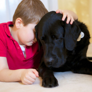 A picture of a young boy with his arm around a black dog, leaning his forehead against the dog's ear.