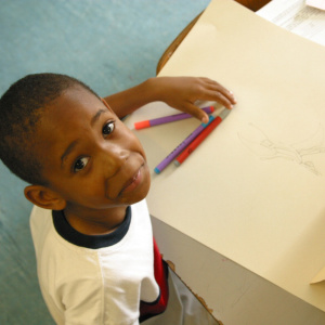 A picture of a young boy taken from above. He is sat at a table with pens and a drawing in front of him, and his head is tilted upwards, looking at the camera and smiling slightly.