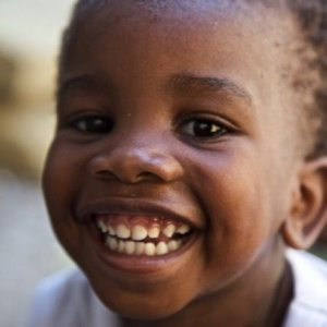 A close up of a young child who is smiling and showing all his teeth.
