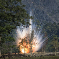 A photo of a large explosion, with sparks flying. In the background is a rock cliff face, and in the foreground some small trees.