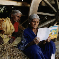 A picture of two elderly women sitting on a bale of hay looking at a book which one of the women is holding open.