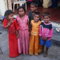 A picture of a group of young children standing together and smiling at the camera.