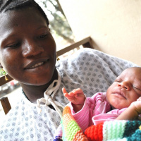 A picture of a young girl in a hospital gown holding a new born baby wrapped in a blanket and looking down at the child.
