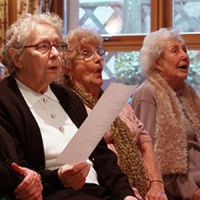 A picture of three elderly women standing in a row and singing, the one on the left is holding up a sheet of paper.