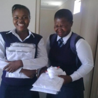 Two girls in school uniform standing next to each other and holding new white shirts in their hands. The girl on the left is smiling widely and the girl on the right is laughing with her eyes shut.