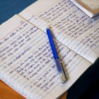 A close up picture of an open notebook, the pages filled with handwriting and a blue pen lying across the middle.