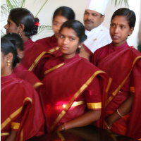 A photo of several young women in red and gold saris standing in a group, behind them is a man in chef's clothes.