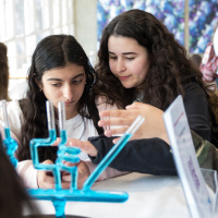 Two teenage girls are in a lab, leaning in to look at something. In front of them are some test tubes containing a blue liquid.