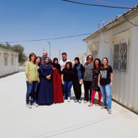 A picture of a group of people standing together in a bare street, with simple houses on each side. Some of them are wearing long dresses and hijabs and some of them are wearing jeans and t-shirts.