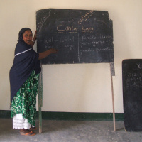 A woman is standing next to a chalk boards with words written on it. She is looking at the camera and smiling.