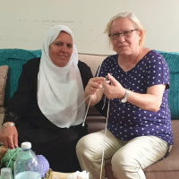 A picture of two women sitting on a sofa together, one wearing a hijab and the other dressed in Western clothes and holding a pair of knitting needles in her hands.