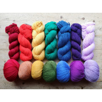 A picture of 7 hanks and 7 balls of yarn laid out on a table. The first ball and hank is red, the next orange, then yellow, then green, then blue, then purple, then violet - making a rainbow.