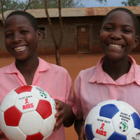 A close up of two children standing next to each other holding footballs and smiling with joy.
