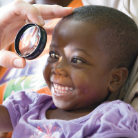 A close up picture of a very young child who is smiling widely. There is a hand holding an eye glass in front of one of her eyes.