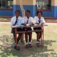 Three teenage girls in school uniform sat at a desk outside, with notebooks on the table.